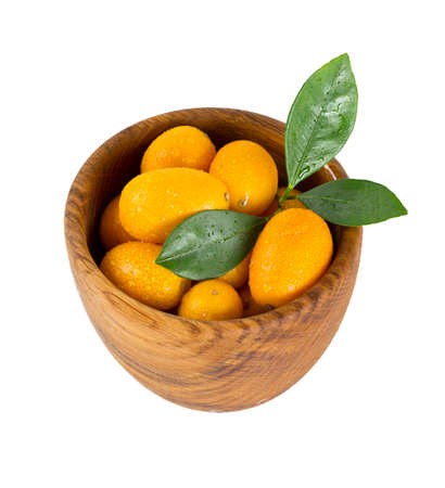 cumquat: cumquat in wooden bowl isolated on white