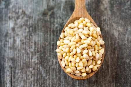 pine kernels: pine nuts in a wooden spoon Stock Photo
