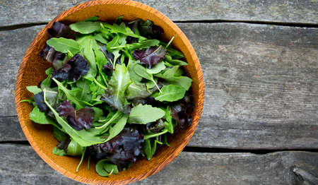 fresh green salad mix in a wooden bowl