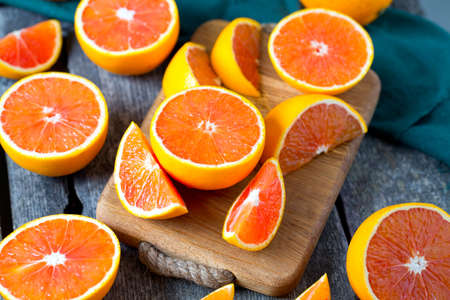 orange slices: red oranges on wooden surface Stock Photo