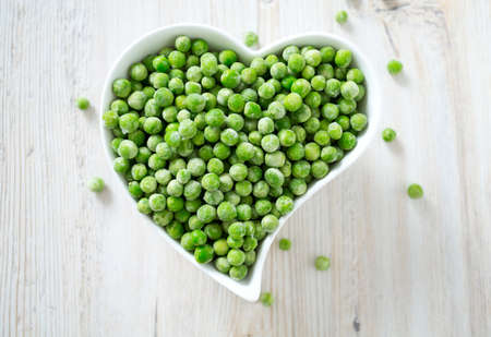 frozen peas on wooden surface