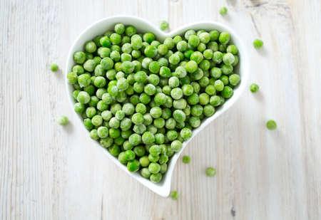frozen peas on wooden surface
