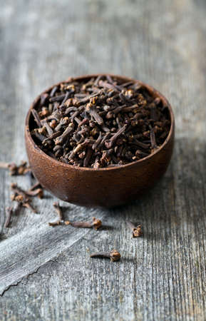 cloves in a bowl on wooden surface