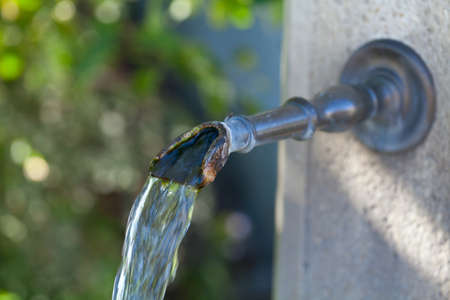source of water: Closeup of water running from outdoor wall faucet Stock Photo