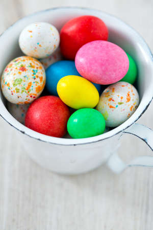 dring: Easter candy eggs on white wooden surface