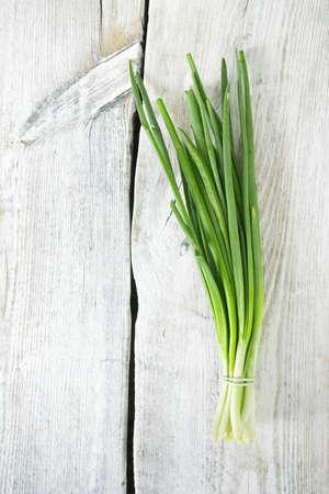 scallion: fresh onion on wooden surface