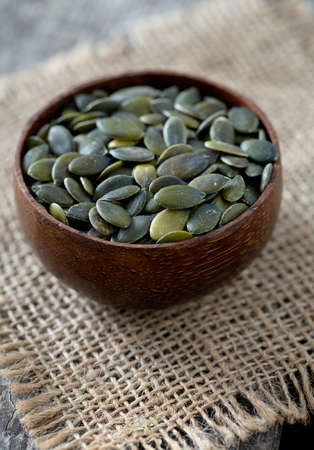 pumpkinseed: pumpkin seeds in a bowl over wooden surface Stock Photo
