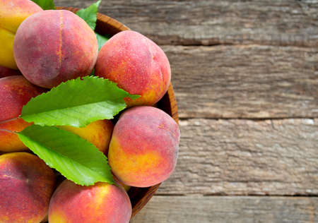 wooden basket: ripe peaches on wooden surface Stock Photo