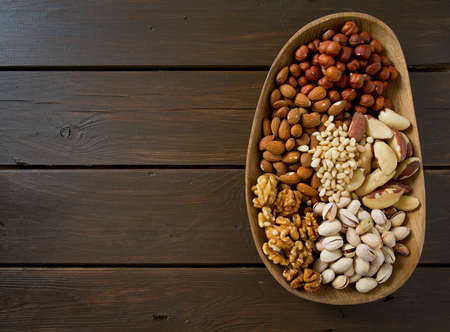 pine kernels: different knds of nuts in a wooden plate Stock Photo