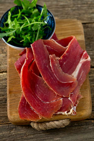 jamon: jamon and rucola on wooden surface