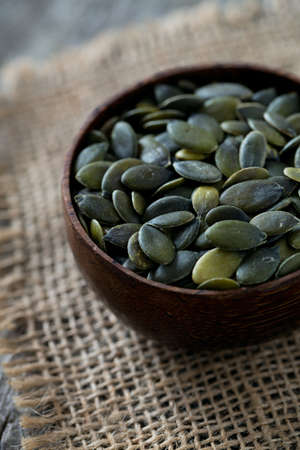 pumpkin seeds in a bowl over wooden surface Stock Photo