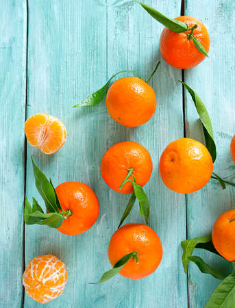 tangerines with green leaves on turquoise wooden background