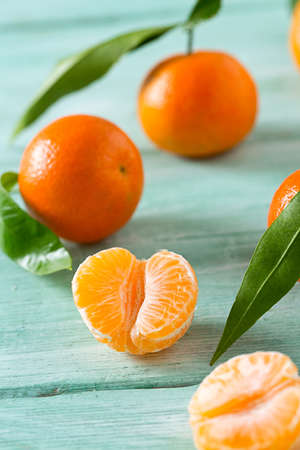 sweet segments: tangerines with green leaves on turquoise wooden background
