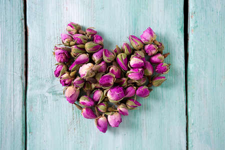 potpourri: dried rose buds on turquoise wooden surface Stock Photo