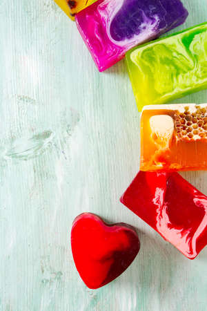 colorful hand made soap bars on turuoise wooden surface