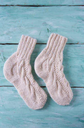 white knitted socks on turquoise wooden surface Stock Photo