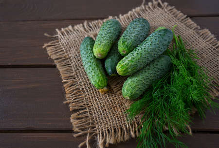 full willow: cucumber harvest on wooden surface Stock Photo