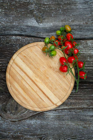 round cutting board and tomatoes on wooden surface Stock Photo