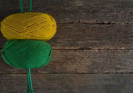 colorful yarn and knitting needles on rustic wooden surface Фото со стока