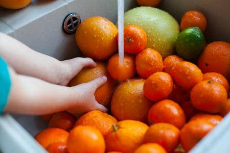 cute boy is washing citrus fruits