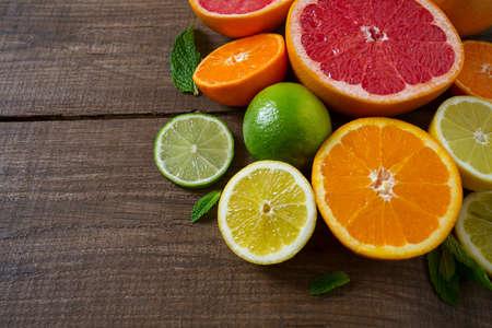 mixed citrus fruits on dark wooden background