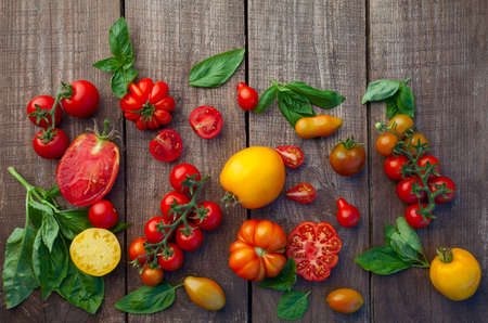 fresh organic colorful tomatoes on wooden surface