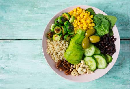Buddha Bowl mit Rosenkohl, Mais, Quinoa, Gurken, Nüssen, Avocado und Spinat