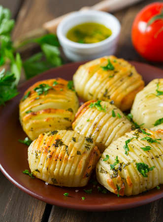 Hasselback potatoes on wooden surface