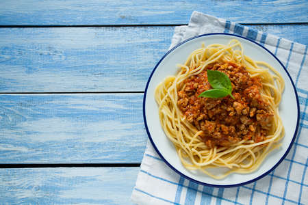 spaghetti bolognese on wooden surface