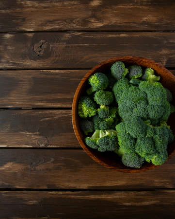 broccoli in a bowl on wooden surface