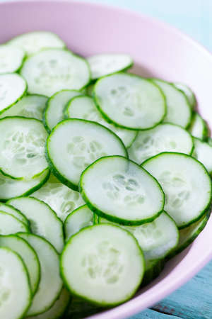 cucumbers in a bowl on turquoise surface Standard-Bild - 124532272