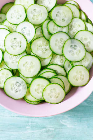 cucumbers in a bowl on turquoise surface Standard-Bild - 124532434