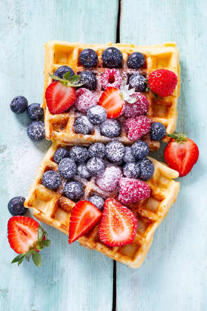 belgian waffles with berries on turquoise surface