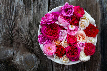 pink,red, violet and white roses on wooden surface