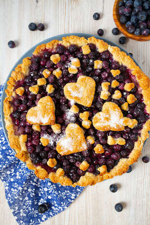 homemade blueberry pie on white wooden surface
