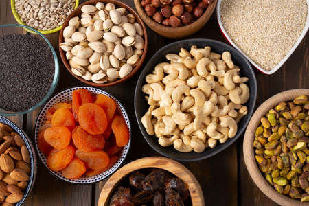 nuts, seeds and dried fruis on wooden surface Standard-Bild - 133207531