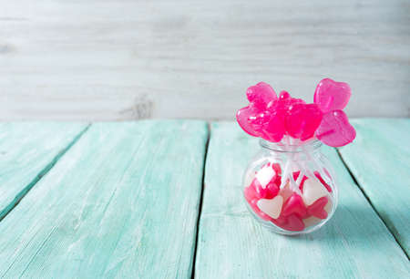 heart-shaped candies on turquoise wooden surface