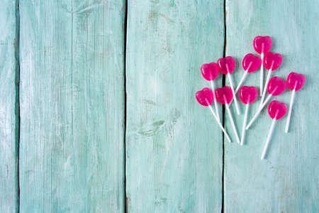 heart-shaped lollipops on turquoise surface 免版税图像