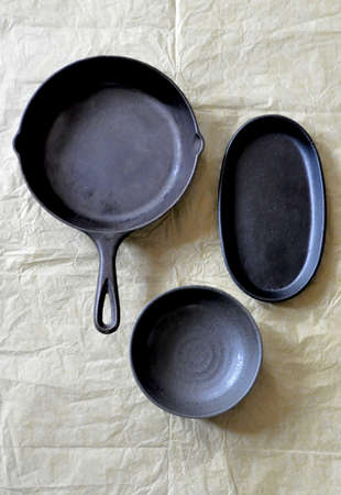 black cast iron frying pan, oval dish, and bowl arranged on a brown background, top view