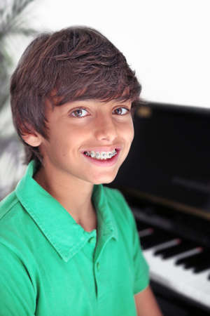 Smile with braces: boy at the piano smiling