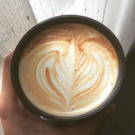 art: Coffee latte art in cup by the window