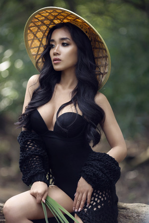 young sexy Vietnamese girl in a straw hat in a tropical forest. asian girl
