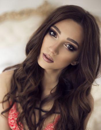 mooie jonge sexy meid met make-up en krullen. mode maakt zwarte ogen