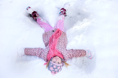 girl snow angel. trail of an angel in the snow, children have fun in the winter before the new year Stock Photo