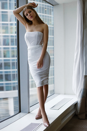 beautiful girl near the window of the metropolis. big city and girls. female beauty is the ideal figure. sadness and memories at the window