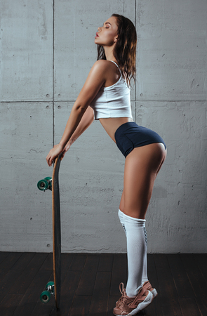 Fitness girl in a white top and short shorts standing with a skateboard on background of a concrete wall