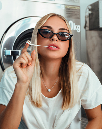 Cheeky young blonde girl chews gum in the laundry