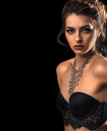 Close-up portrait of a beautiful young woman with velvet skin and black bra. Jewelry on neck. On an isolated black background. Stock Photo