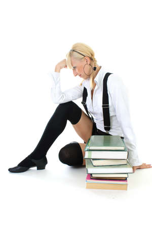 cute schoolgirl in school form sitting with books photo