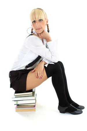 cute schoolgirl sitting on stacked books photo